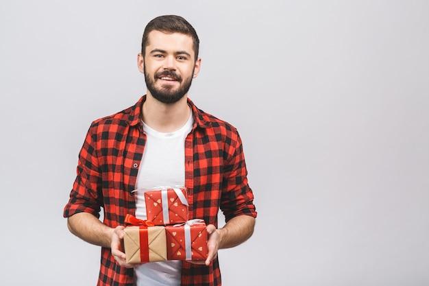 Porträt eines aufgeregten jungen bärtigen mannes, der viele geschenke trägt, lokalisiert auf weißem studiohintergrund.