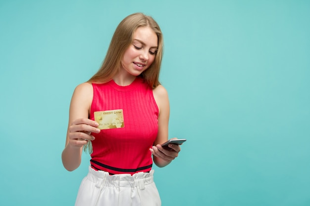 Porträt eines aufgeregten jungen mädchens, das plastikkreditkarte zeigt, während handy hält