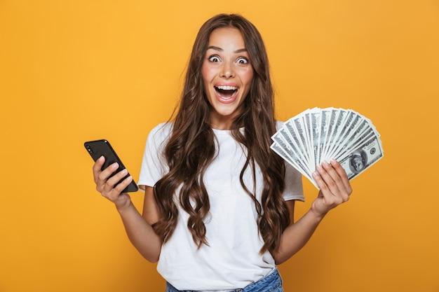 Porträt eines aufgeregten jungen mädchens mit langen brünetten haaren, die über gelber wand stehen und geldbanknoten halten, unter verwendung des mobiltelefons