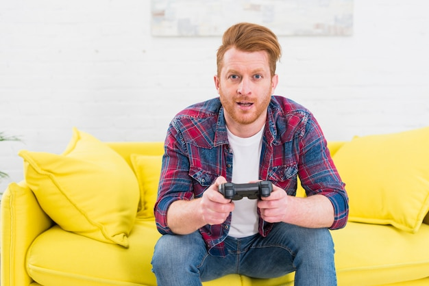 Porträt eines aufgeregten jungen mannes, der auf dem gelben sofa spielt das videospiel sitzt
