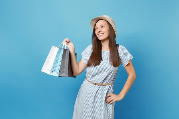 Porträt eines aufgeregten lächelnden schönen mädchens, das sommerkleid trägt, hut nach oben schaut, pakettaschen mit einkäufen nach dem einkaufen einzeln auf blauem pastellhintergrund hält. kopieren sie platz für werbung.