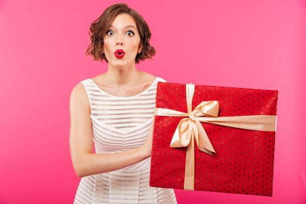 Porträt eines aufgeregten mädchens kleidete im kleid an, das geschenk hält
