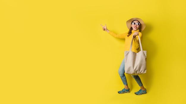 Porträt eines aufgeregten schönen mädchens, das ein kleid und eine sonnenbrille trägt, die einkaufstaschen halten. fröhliche junge frau mit handtasche auf gelbem hintergrund. shopaholic shopping mode.