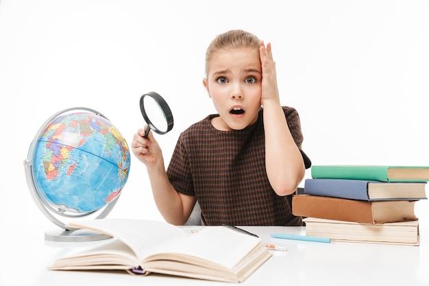 Porträt eines aufgeregten schulmädchens, das bücher liest und hausaufgaben macht, während es am schreibtisch in der klasse sitzt, isoliert über weißer wand