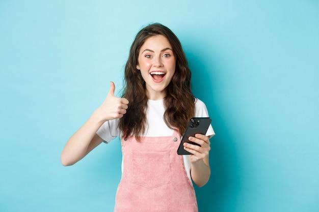 Porträt eines aufgeregten süßen mädchens sagt ja, lächelt und nickt zustimmend, hält smartphone, während es daumen zeigt, wie und lobt gutes online-angebot, das vor blauem hintergrund steht.