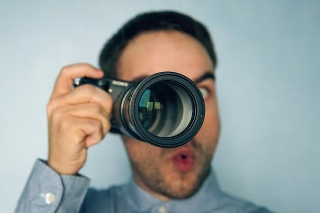 Porträt eines aufgeregten überraschten fotografen mit kamera zur hand. reporter macht eine erstaunliche aufnahme. fotograf überrascht von dem bild. die paparazzi verfolgen das motiv durch ein großes teleobjektiv