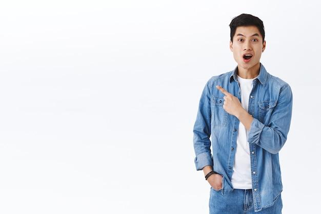 Porträt eines aufgeregten und beeindruckten asiatischen mannes, der ein tolles ereignis in der nähe hört, blicken sie mit der kamera erstaunt auf den offenen mund, der über das produkt auf der linken seite des kopierraums spricht und auf die promo zeigt