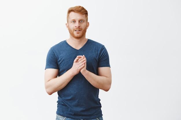 Porträt eines aufgeregten und faszinierten gutaussehenden geschäftsmannes mit ingwerhaar und borsten, die handflächen nahe brust berühren und mit neugierigem ausdruck lächeln