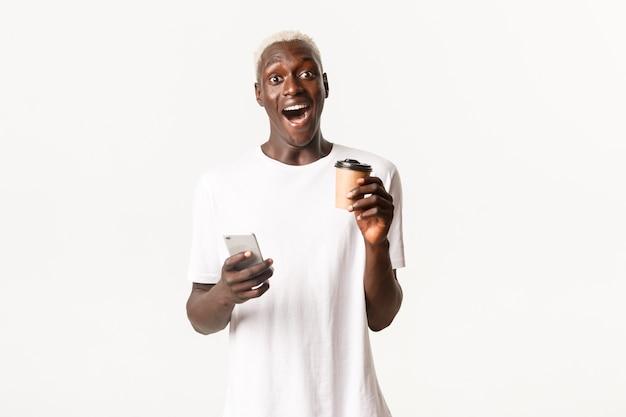 Porträt eines aufgeregten und verblüfften blonden afroamerikaners, der fasziniert aussieht, handy benutzt und kaffee trinkt