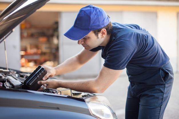 Porträt eines automechanikers, der öl in einen automotor einsetzt