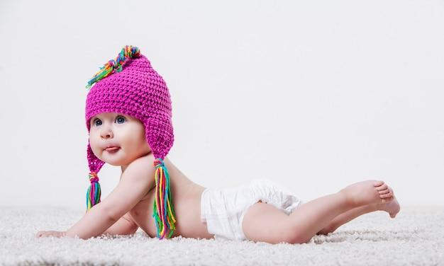 Porträt eines babys mit rosa wollmütze und farbigen fransen