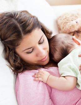 Porträt eines babys und seiner mutter, die friedlich zu hause im sofa schlafen