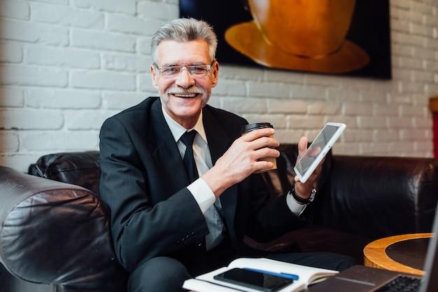 Porträt eines bärtigen älteren mannes, der kaffee in einem café trinkt. älterer mann mit intelligentem laptop im café.