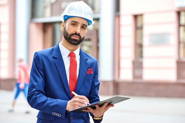 Porträt eines bärtigen arabischen architekten mit einem klemmbrett in seinen händen copyspace an der seite