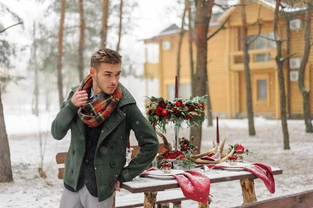 Porträt eines bärtigen bräutigams in einem eleganten anzug mit hosenträgern und fliege im winter in einem skigebiet