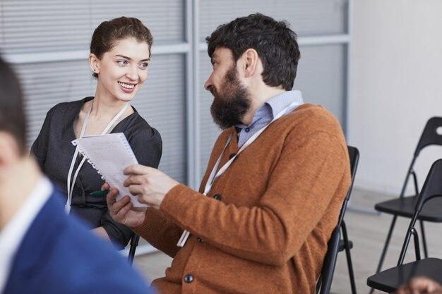 Porträt eines bärtigen geschäftsmannes, der mit einer lächelnden jungen frau spricht, während er im publikum auf einer geschäftskonferenz sitzt, platz kopieren