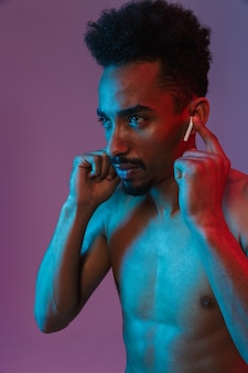 Porträt eines bärtigen, hemdlosen afroamerikaners, der mit ohrstöpsel über violetter wand isoliert posiert