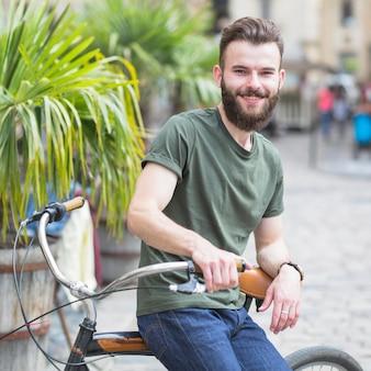 Porträt eines bärtigen jungen männlichen radfahrers, der auf fahrrad sitzt