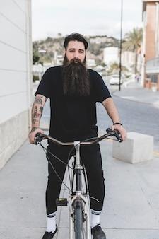 Porträt eines bärtigen jungen mannes, der auf fahrrad sitzt