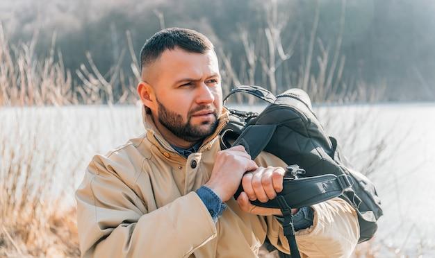 Porträt eines bärtigen mannes, der auf einem baumstamm nahe dem see sitzt. kaukasischer mann, der allein auf dem see sitzt und eine ansicht an einem sommertag betrachtet.
