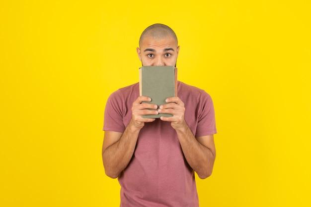 Porträt eines bärtigen mannes, der bucheinband über gelber wand zeigt.