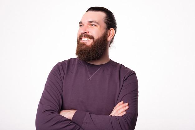 Porträt eines bärtigen mannes, der mit verschränkten armen sitzt und lächelnd wegschaut