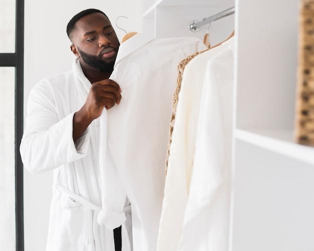 Porträt eines bärtigen mannes, der seine garderobe überprüft