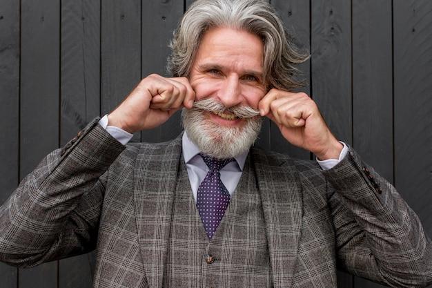 Porträt eines bärtigen mannes, der seinen schnurrbart berührt