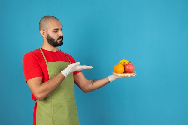 Porträt eines bärtigen mannes in schürze, der ein holzbrett mit frischen früchten hält.
