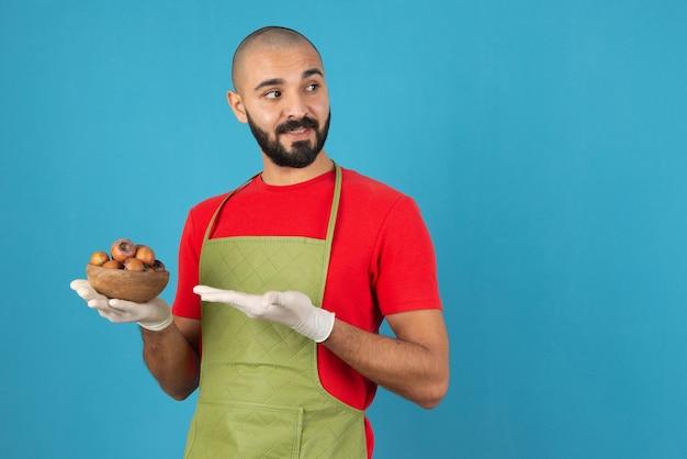 Porträt eines bärtigen mannes in schürze, der eine holzschale mit getrockneten früchten hält.