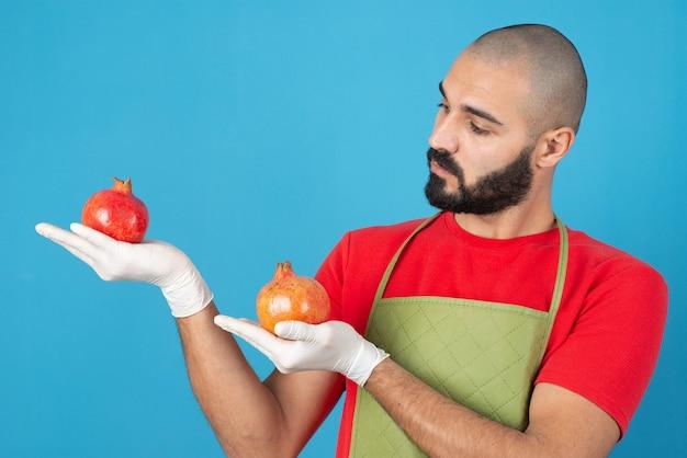 Porträt eines bärtigen mannes in schürze, der zwei frische granatäpfel in den händen hält.