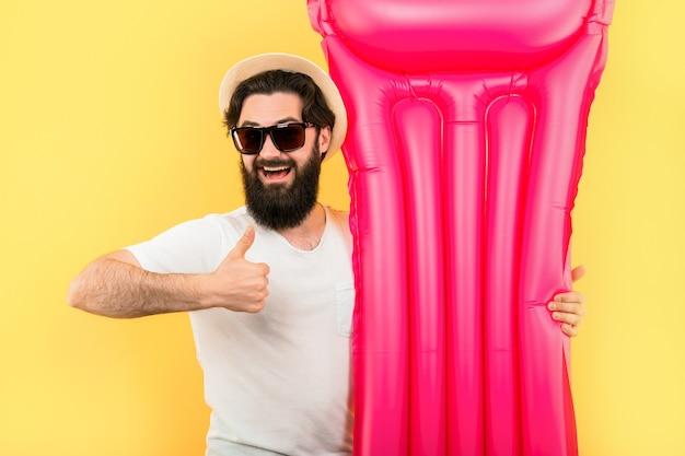 Porträt eines bärtigen mannes in sonnenbrille und hut mit rosa aufblasbarer schwimmmatratze