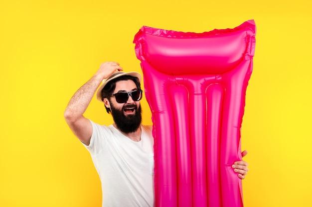 Porträt eines bärtigen mannes in sonnenbrille und hut mit rosa aufblasbarer schwimmmatratze Premium Fotos