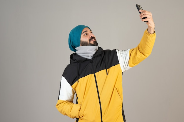 Porträt eines bärtigen mannes in warmer kleidung, der mit seinem handy ein selfie macht.