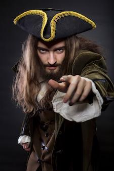 Porträt eines bärtigen und haarigen piraten, der in den betrachter zeigt, flacher dof