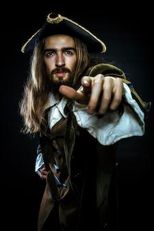 Porträt eines bärtigen und haarigen piraten, der in die ferne zeigt, flacher dof