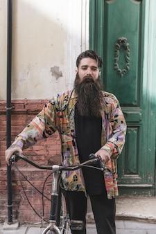 Porträt eines bartmannes mit seinem fahrrad, das kamera betrachtet