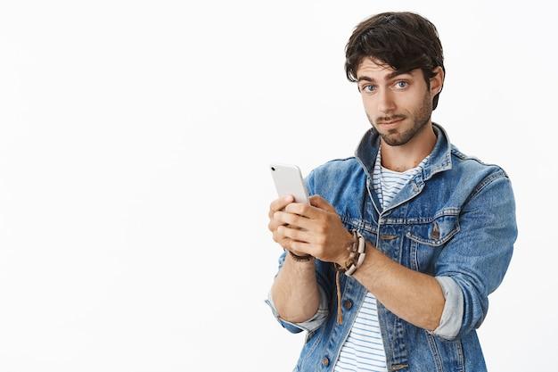 Porträt eines beeindruckten, gut aussehenden europäischen männchens mit borsten und blauen augen in trendiger jeansjacke, das smartphone mit hochgezogenen augenbrauen hält und zufrieden nach vorne blickt