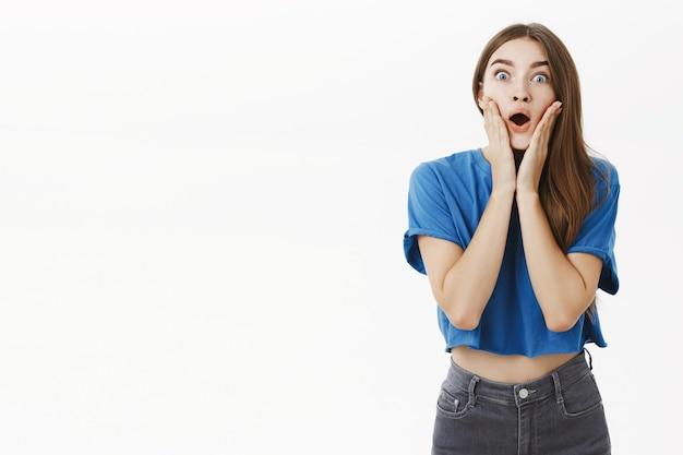 Porträt eines beeindruckten und erstaunten klatschmädchens mit braunen haaren im blauen t-shirt, das vor erstaunen und überraschender berührung der wangen nach luft schnappt