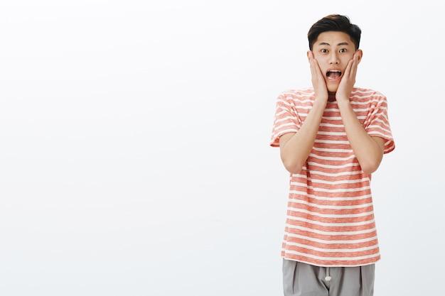 Porträt eines beeindruckten und überraschten aufgeregten jungen asiatischen männlichen studenten, der vor erstaunen und freude schreit, die hände auf die wangen drückt und begeistert und erstaunt auf die rechte seite des kopierraums starrt