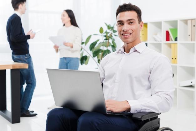 Porträt eines behinderten lächelnden jungen geschäftsmannes, der auf rollstuhl mit laptop und geschäftskollegen im hintergrund sitzt
