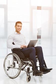 Porträt eines behinderten lächelnden jungen geschäftsmannes, der auf rollstuhl unter verwendung des laptops im büro sitzt