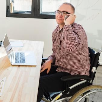 Porträt eines behinderten mannes, der im büro arbeitet