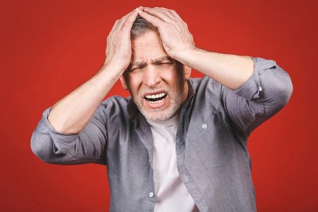 Porträt eines benommenen verärgerten besorgten traurigen, depressiven, müden älteren mannes mit kopfschmerzen, sehr gestresster, isolierter, negativer menschlicher gefühlsausdruck.
