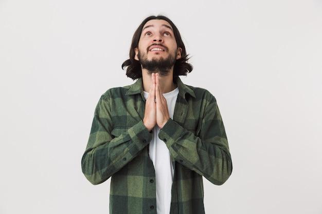Porträt eines besorgten jungen bärtigen brünetten mannes mit kariertem hemd, der isoliert über weißer wand steht und betet