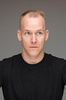 Porträt eines blonden kaukasischen mannes im schwarzen t-shirt, der mit weit geöffneten augen wegschaut und überraschung oder schock zeigt.