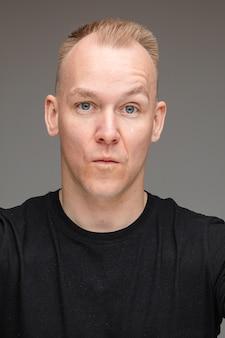 Porträt eines blonden kaukasischen mannes mit blauen augen, die seine augenbraue mit schmollenden lippen anheben, die kamera betrachten. necken und verführen konzept.