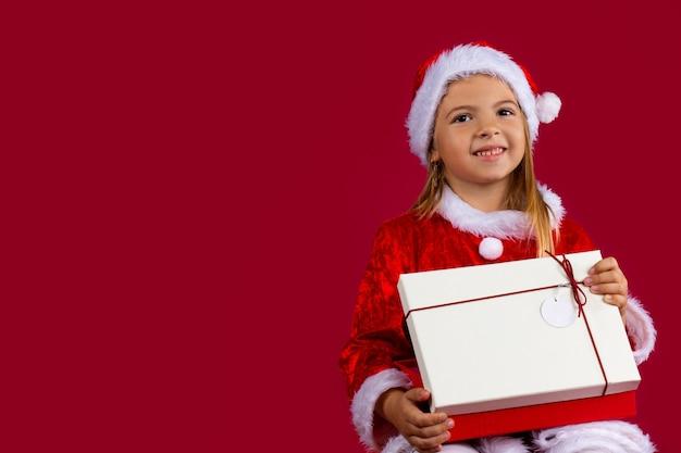 Porträt eines blonden kleinen mädchens im weihnachtsmannkleid. auf einer roten isolierten wand mit leerem seitenraum. .