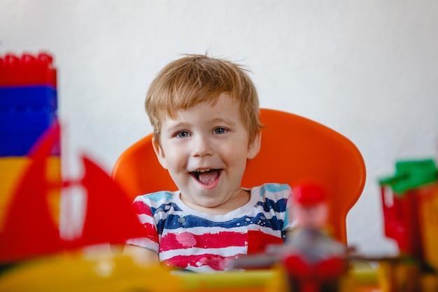 Porträt eines blonden lachenden kleinen jungen unter bunten plastikspielzeugen. hochwertiges foto