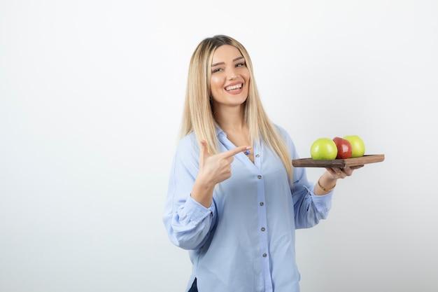 Porträt eines blonden mädchens, das auf holzbrett mit grünen und roten äpfeln zeigt